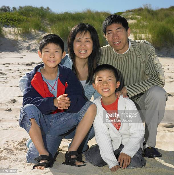 Family smiling for the camera on the beach