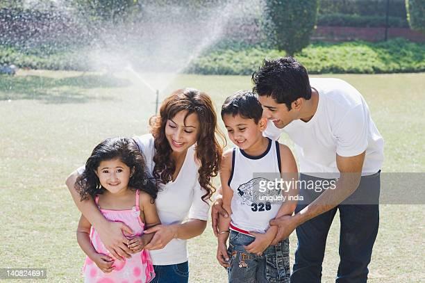 Family smiling in front of a sprinkler, Gurgaon, Haryana, India