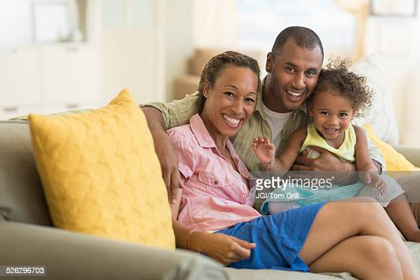 Family smiling on sofa in living room