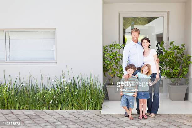 Family smiling outside front door