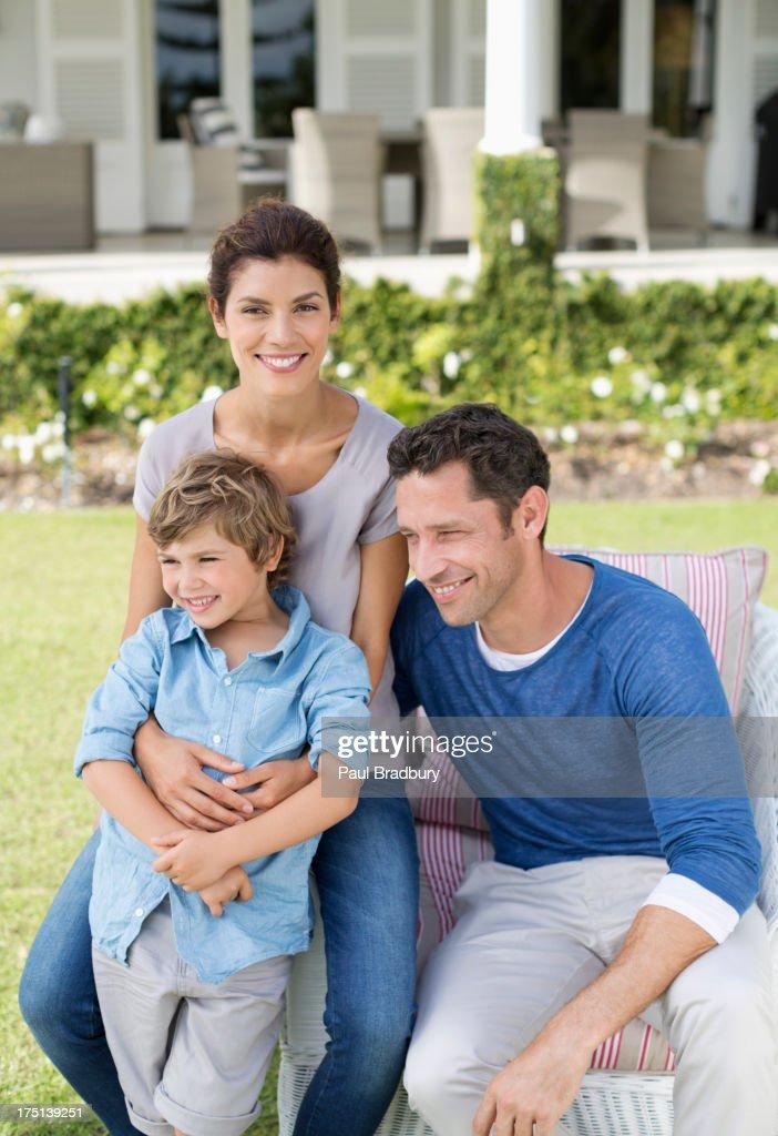 Family smiling outside house : Stock Photo