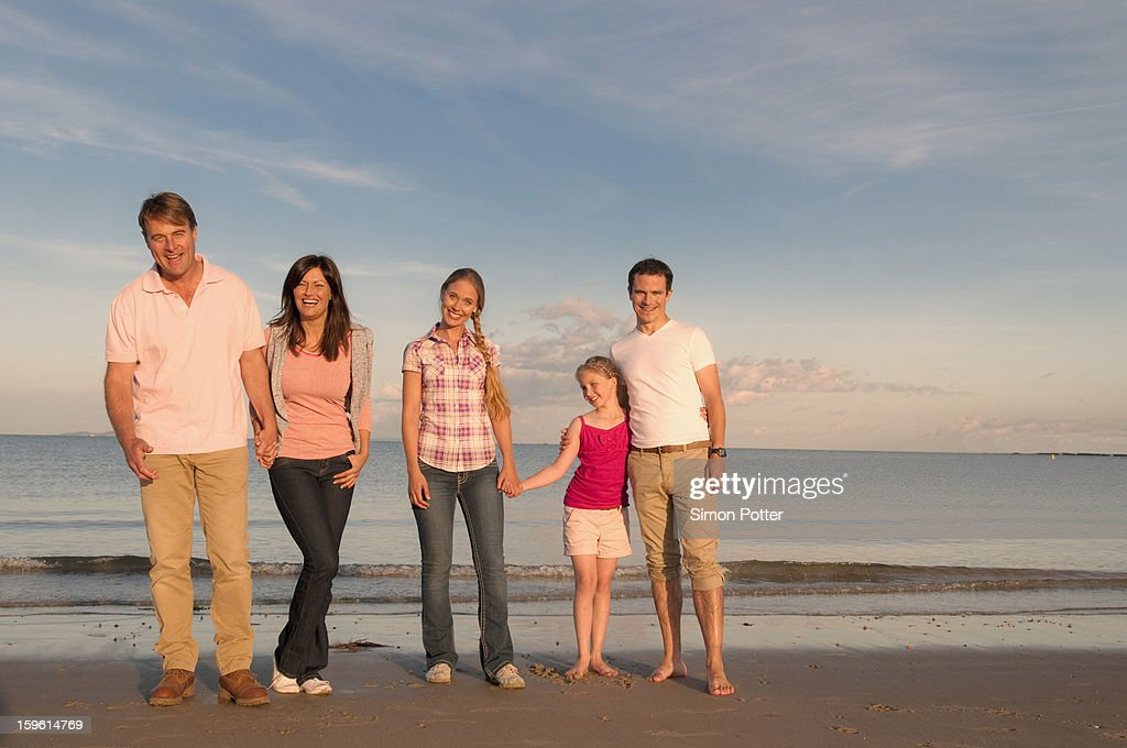 Family smiling together on beach : Stock Photo