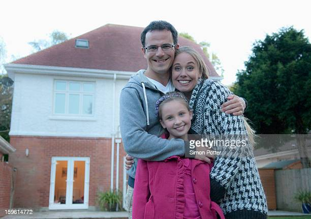 Family smiling together outside house