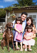 Family smiling together with dog in backyard