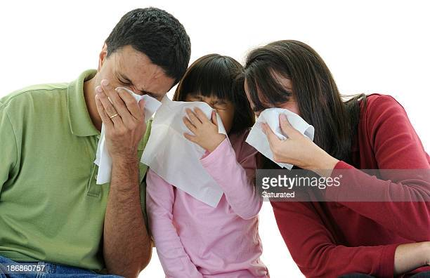 Family Sneezing Into Tissues