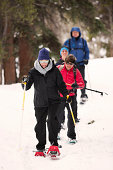 A family snow shoeing in the woods.