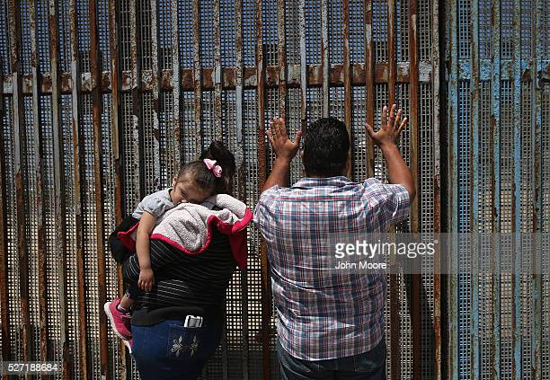 A family speaks through the USMexico border fence on May 1 2016 in Tijuana Mexico They came to see family member 'dreamers' who immigrated as...
