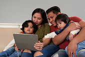 Asian family gathered together to watch a movie on tablet computer