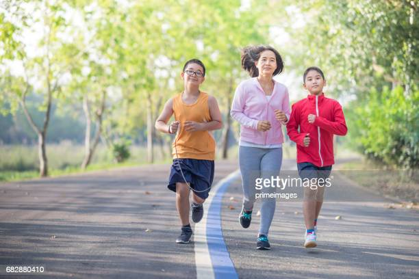 Family sport happy active mother and kids jogging outdoors running in forest
