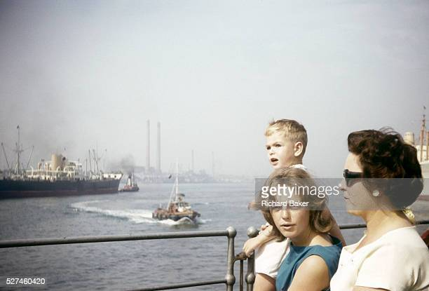 A family stand at railings watching shipping on the River Thames at Gravesend during summer time in the early 1960s Standing at some railings the two...