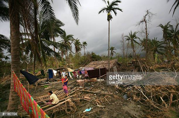 A family stand by what is left of their home at the isolated village of Myasein Kan on May 20 2008 in the Ayeyarwaddy delta Myanmar It has been...