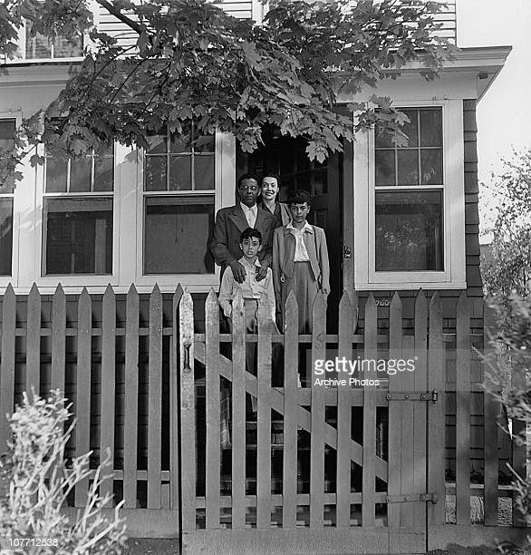 A family stand outside their family home complete with picket fence circa 1950's