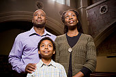 Family Standing and Praying in Church
