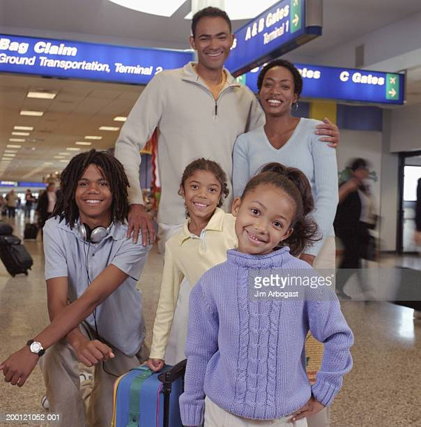 Family standing at baggage claim in airport, portrait