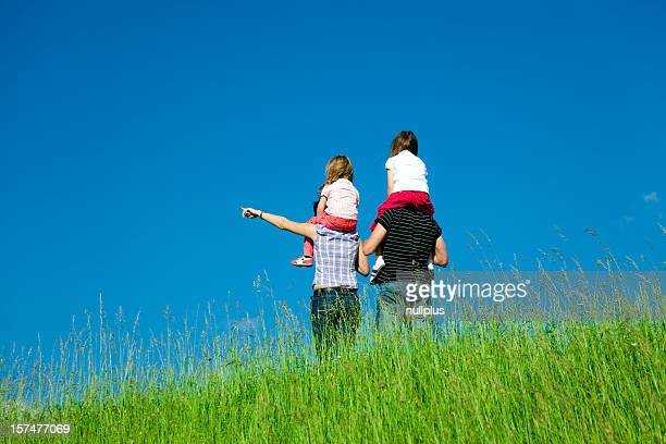 family standing at the top of a hill