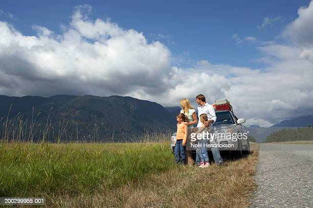 Family standing beside car in rural landscape, looking at scenery