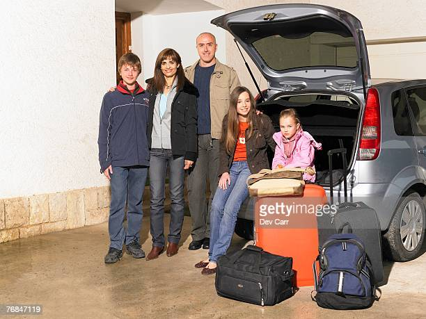 Family standing by car and luggage, portrait