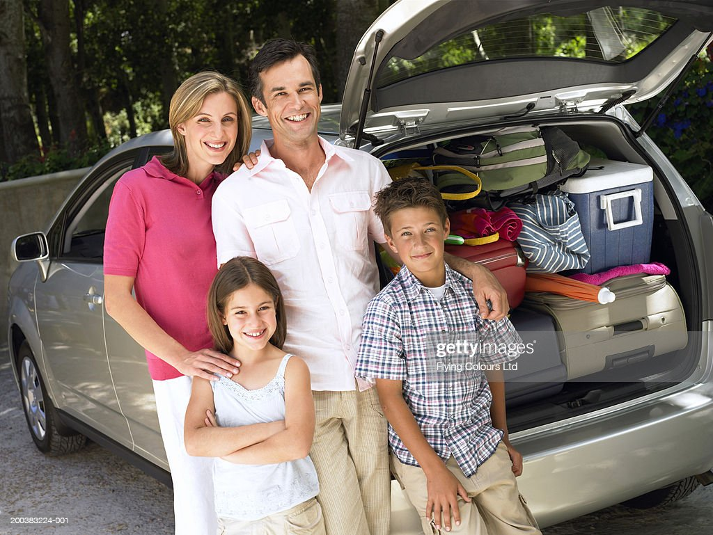 Family standing by car loaded with cases, smiling, portrait : Stock Photo