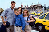 Family standing by taxi