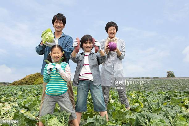 Family standing in cabbage field