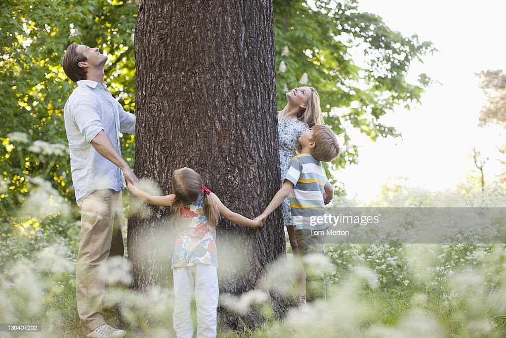 Family standing in circle around tree : Stock Photo