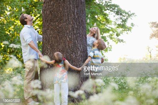 Family standing in circle around tree : Stock Photo