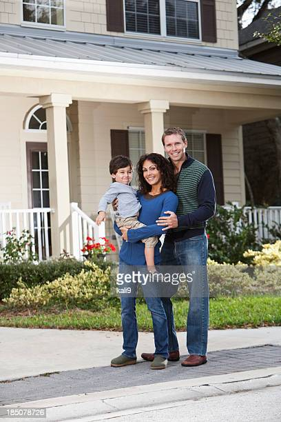 Family standing in front of house