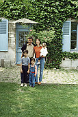 Family standing in front of house, portrait