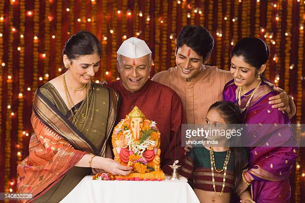 Family standing in front of the idol of lord Ganesha