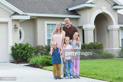 Family standing in front yard of home