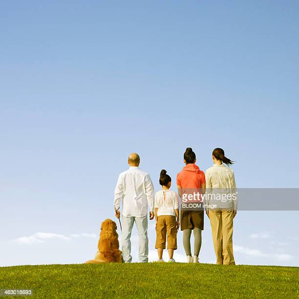 Family Standing In The Park With Dog