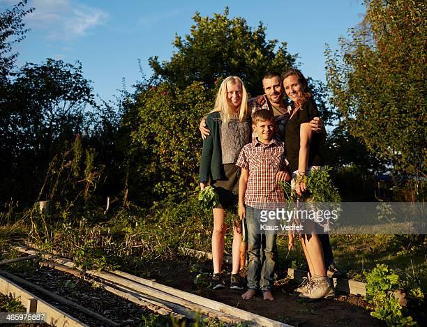 Family standing in their vegetable garden
