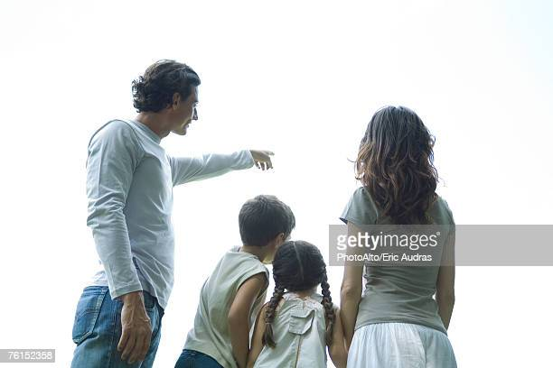 'Family standing looking at sky, rear view, low angle view'