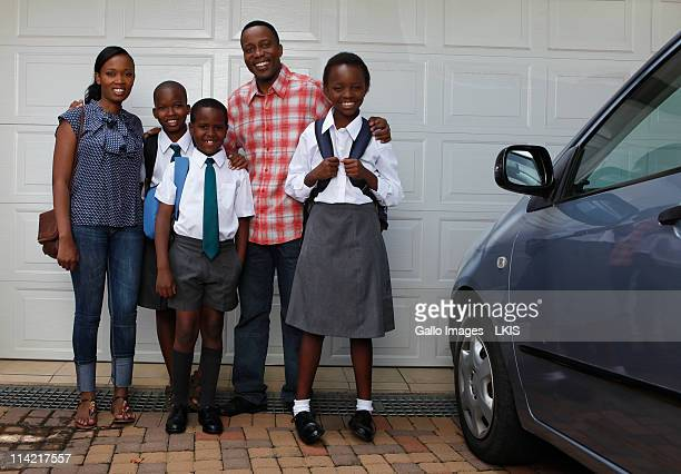 Family standing next to car in driveway, Johannesburg, South Africa