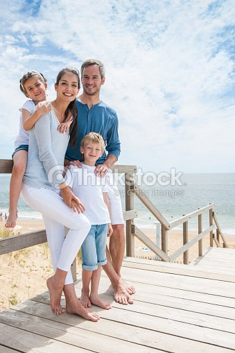 Family standing on a wood pontoon deck by the sea