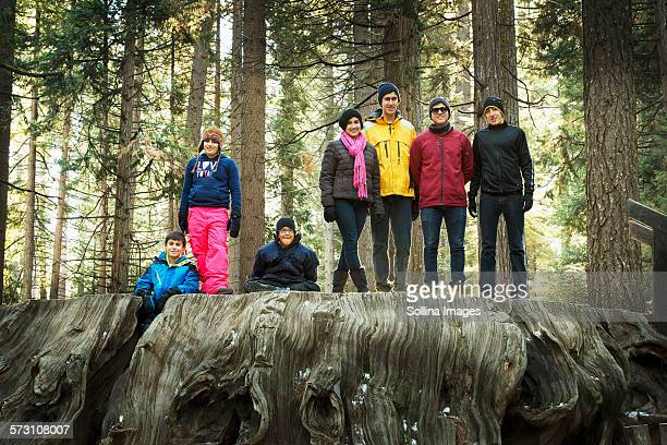 Family standing on enormous stump in forest