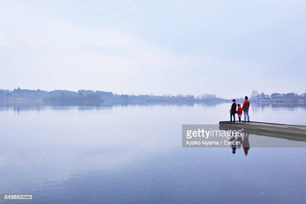 Family Standing On Jetty Looking At Lake View