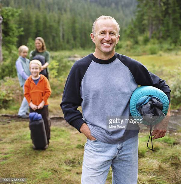 Family standing outdoors, holding sleeping bags, portrait