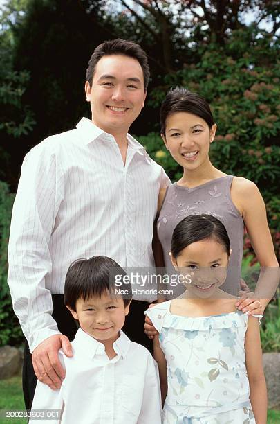 Family standing outdoors, smiling, portrait