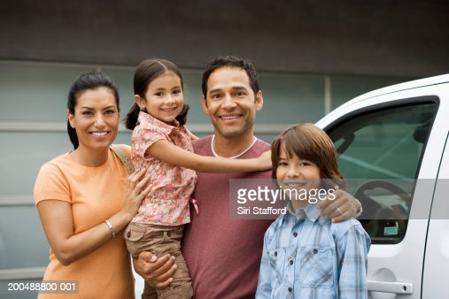 Family standing outside house next to car : Stock Photo
