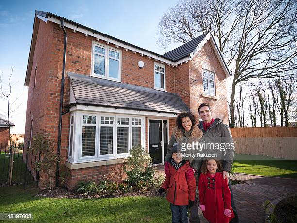 Family standing outside of energy efficient house