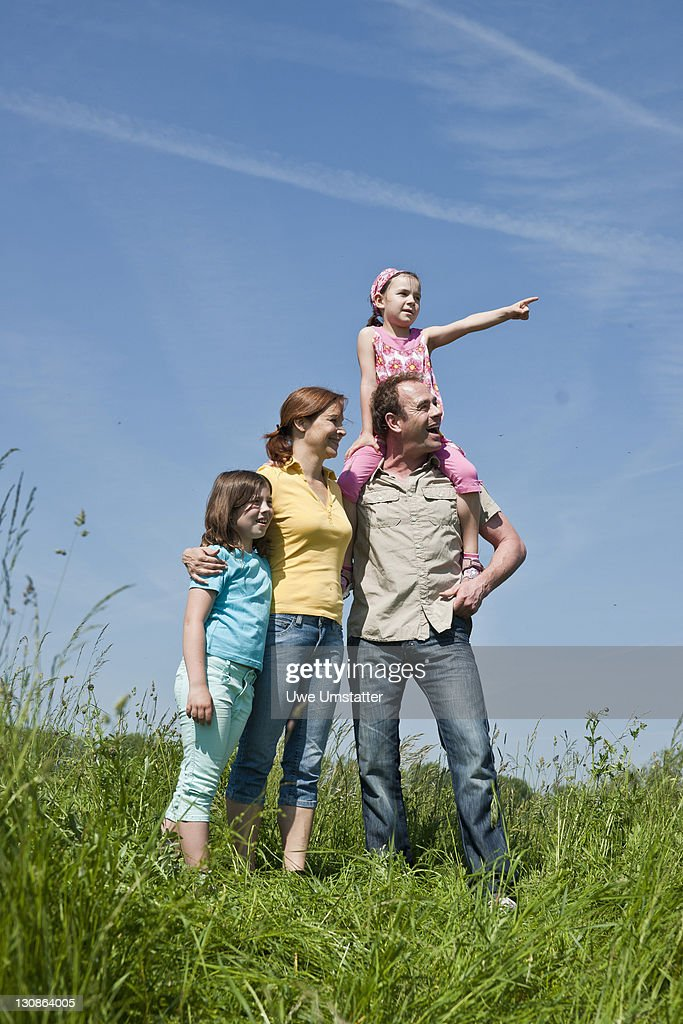 Family standing relaxed in a flower meadow : Stock Photo