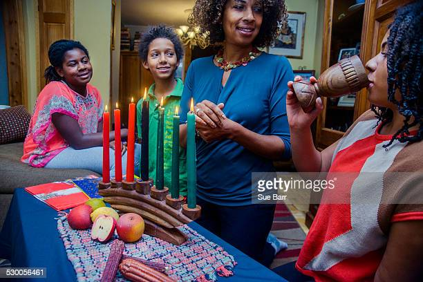 Family standing round lit kinara candles, celebrating Kwanzaa