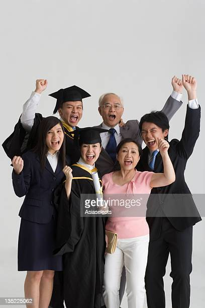 Family standing together and shouting with their hands raised