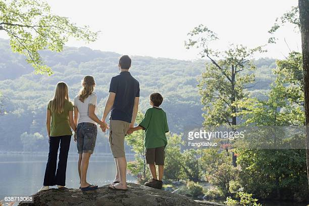Family standing together looking at view of lake in nature