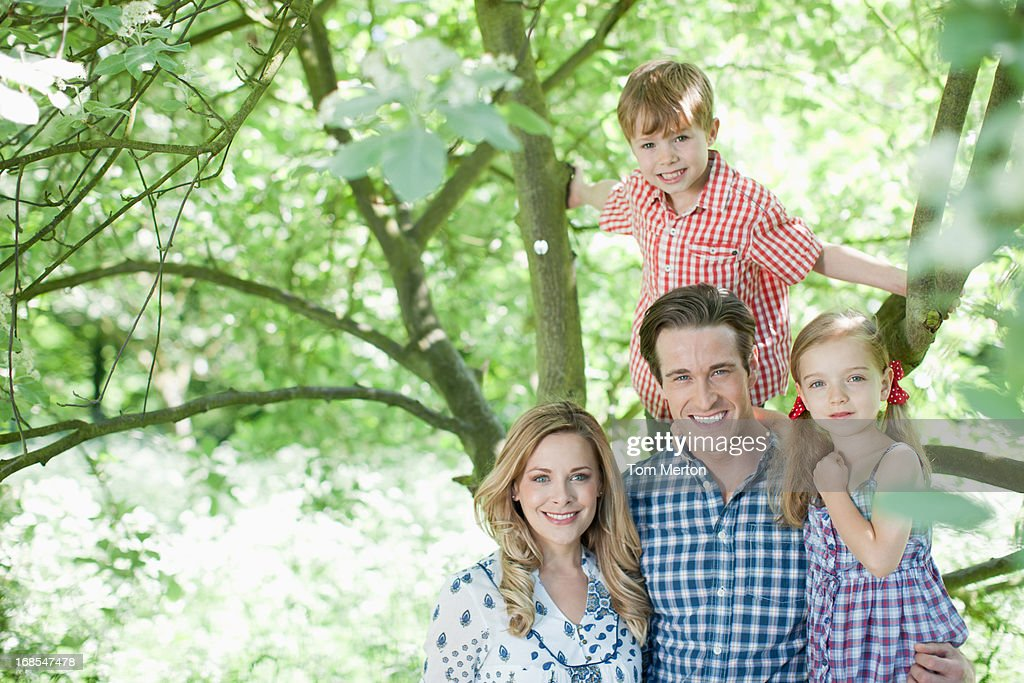 Family standing under tree outdoors : Stock Photo