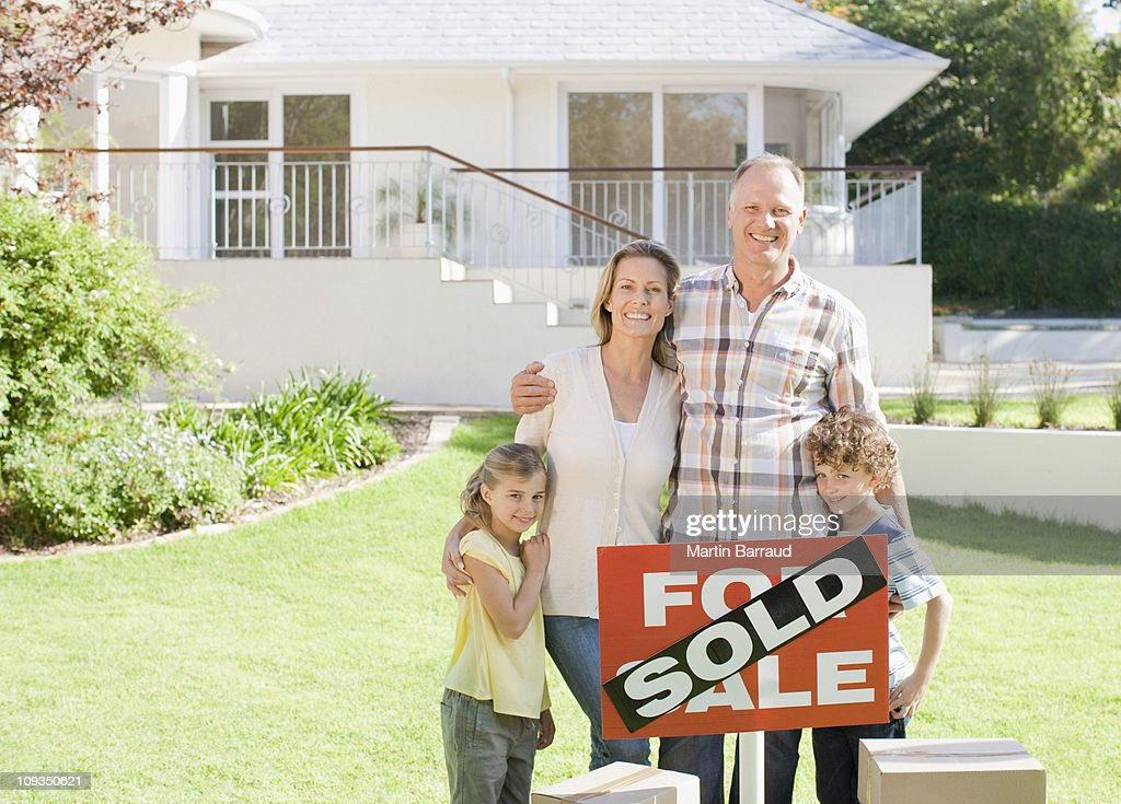 Family standing with sold sign of their new house