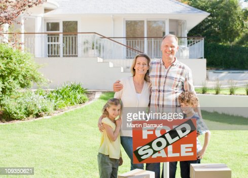 Family standing with sold sign of their new house : Foto de stock
