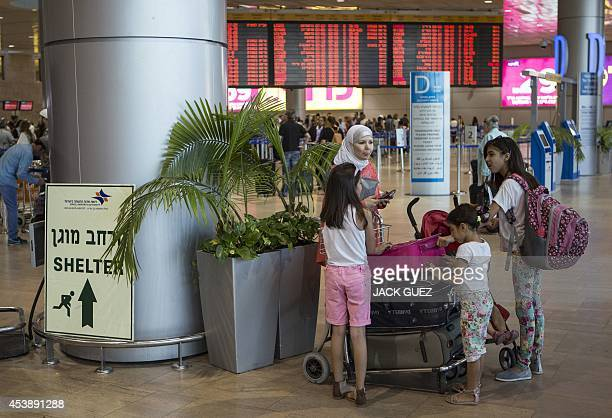A family stands next to a sign directing passengers to a shelter at Ben Gurion International airport near the Mediterranean Israeli coastal city of...