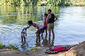 A family stands with their foot on the water the canal Charente in Angouleme on July 19 2016 to cool down as temperature might reach 40° by midday /...